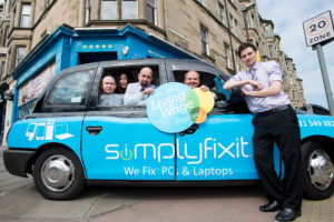 Taxi parked outside SimplyFixIt store at Bruntsfield. Several members of the SimplyFixIt team are also there, inside and outside the taxi.