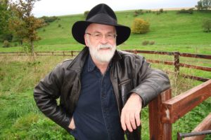 Sir Terry Pratchett leaning against a fence.