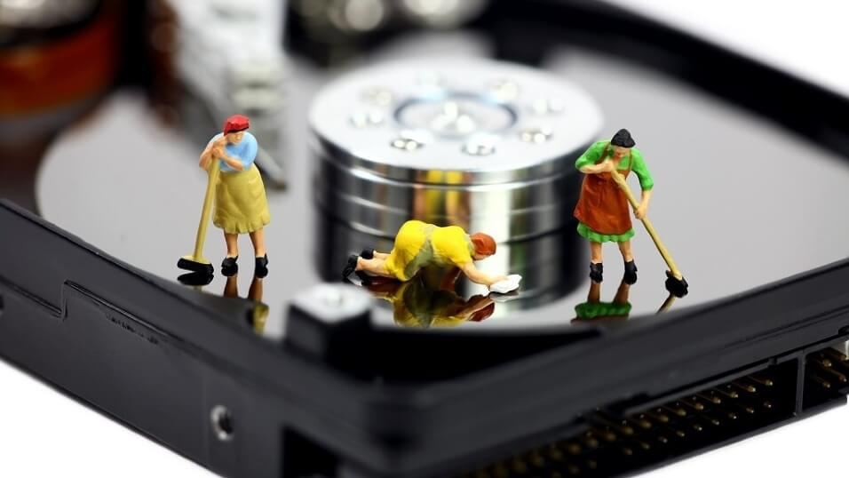 close up view of a hard disk drive with little plastic figures on it. They represent cleaners and they are sweeping and cleaning the hard drive