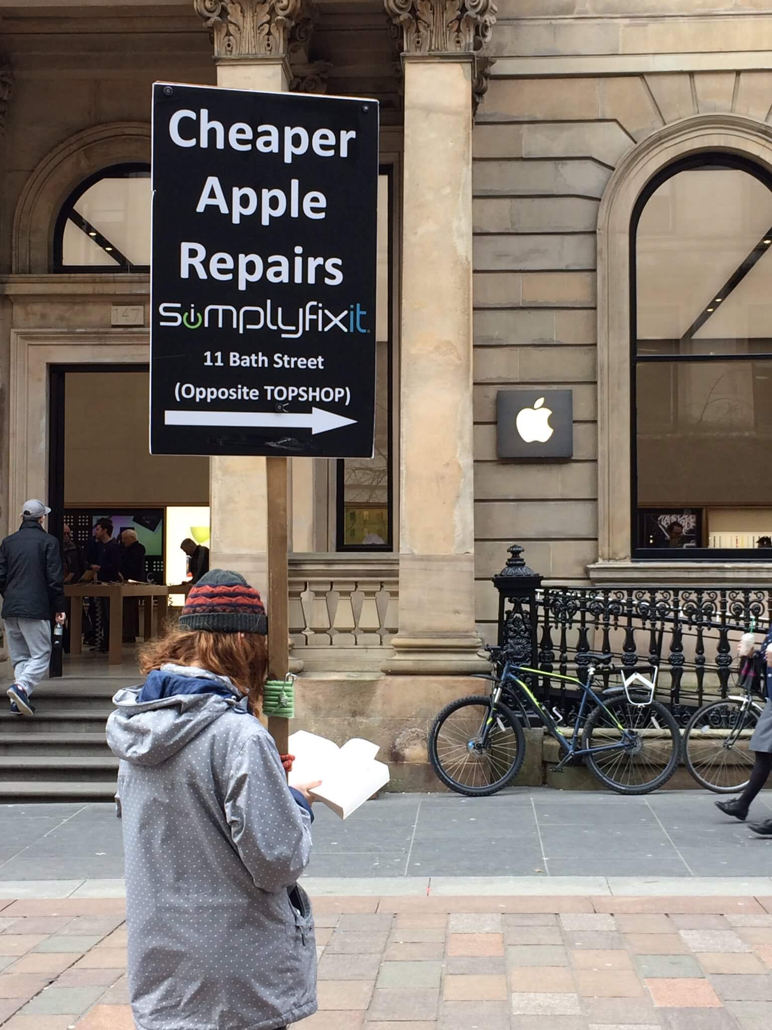 A person holding a golf sale type sign that says, Cheaper Apple repairs at SimplyFixIt